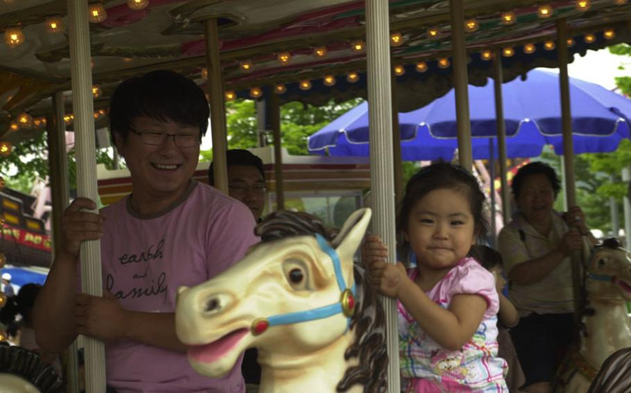 A girl mugs for onlookers as she rides the merry-go-round at Pyeong Hwa Land, a small amusement park near the Civilian Control Line of Korea's Demilitarized Zone. People disagree about whether the park encourages or discourages children from learning about the history and current state of relations between North and South Korea.