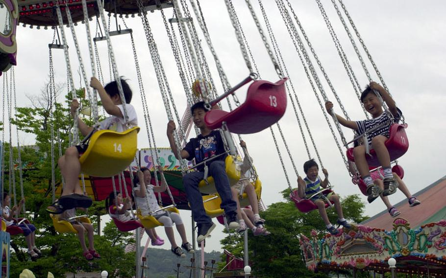Children ride the ''wave swings'' at a small amusement park about 100 yards from what is generally recognized as the southernmost boundary of Korea's Demilitarized Zone.