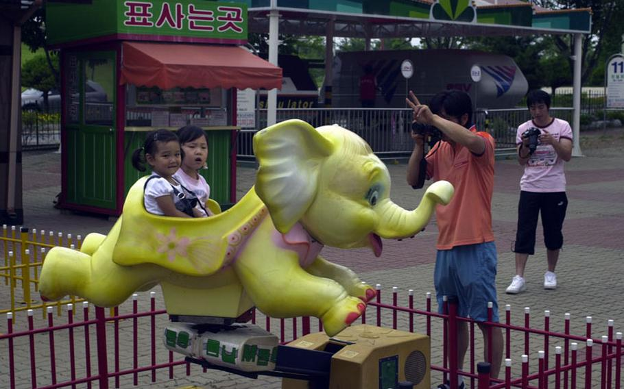 Young girls take a turn on a motorized elephant ride while ignoring the instructions of a camera-toting relative at Pyeong Hwa Land, a small amusement park near Korea's Demilitarized Zone.