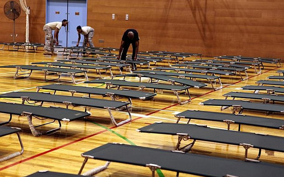 Yokota Air Base personnel at the Samurai Fitness Center begin setting up 400 cots for base residents who had to evacuate their homes due to heavy rain Monday night that led to flooding.