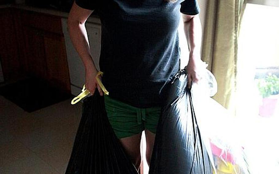 Kendra Weir, a military spouse at Yokota Air Base, carries out trash bags of groceries she cleared out of her refigerator that went bad after heavy rain Monday night led to flooding, power outages and evacuation of some residents from their homes.