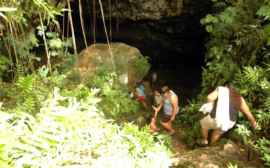 A group of Guam residents climb down to the freshwater caves in the Pagat area, where the island's native Chamorro residents found fresh water thousands of years ago. The military has proposed putting a firing range adjacent to the land, a move that has some residents and local leaders concerned about access to the caves.