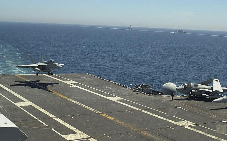 An F-18 Hornet lands on the deck of the USS George Washington on Monday as two warships proceed alongside the aircraft carrier during the Invincible Spirit exercise being staged in the Sea of Japan by the U.S. and South Korea.