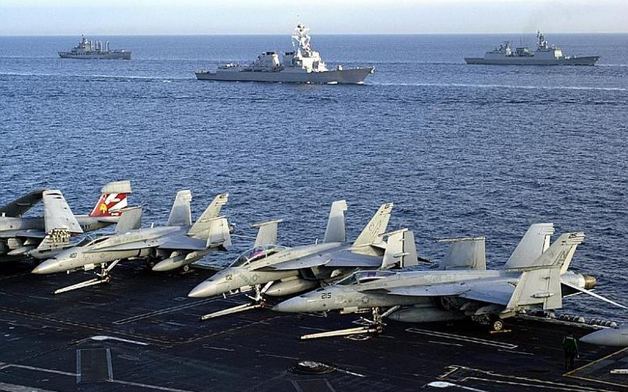 Ships come up close to the deck of the USS George Washington during a tight-formation drill Monday during the Invincible Spirit military exercise the U.S. and South Korea are staging in the Sea of Japan. Twelve ships and a submarine joined in the formation.