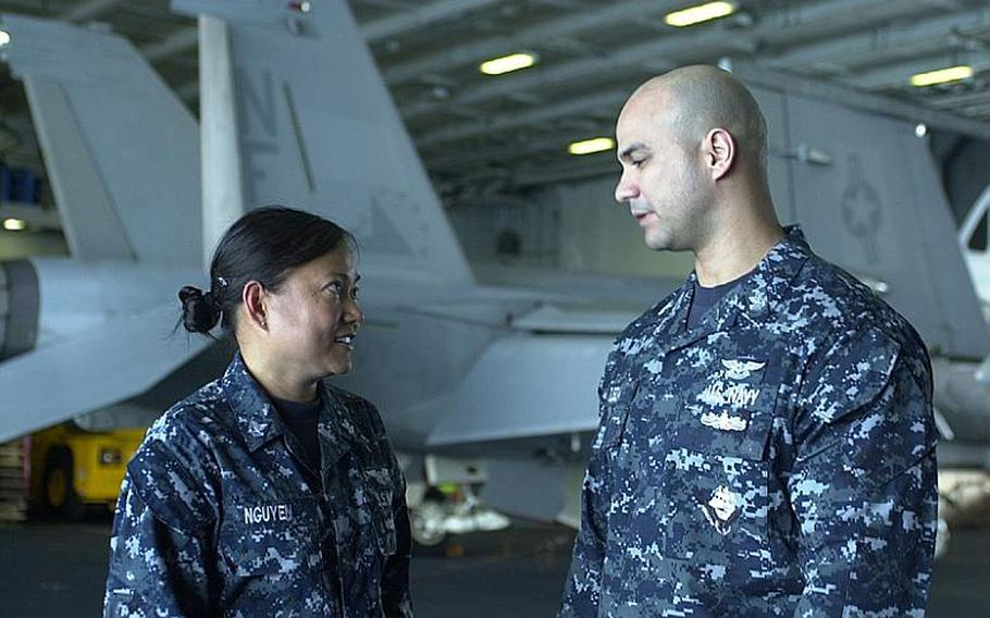 USS George Washington Petty Officer 2nd Class Linhha Nguyen talks to Petty Officer 1st Class Jose Ojeda on Monday aboard the aircraft carrier. Nguyen said the sinking of the South Korean warship Cheonan and the deaths of 46 of its crewmen resonated with U.S. sailors and their families.