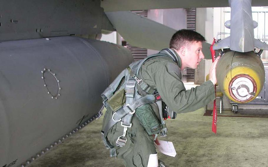 Air Force Capt. Christopher Moeller inspects his F-16C fighter jet Wednesday at Osan Air Base, South Korea, before a combat training mission in which he dropped 500-pound bombs at a training range south of Korea?s Demilitarized Zone. Moeller is with the 36th Fighter Squadron, part of Osan?s 51st Fighter Wing. The mission was one of many combat training sorties flown by U.S. and South Korean aircraft during Invincible Spirit, the four-day exercise that concluded Wednesday night.