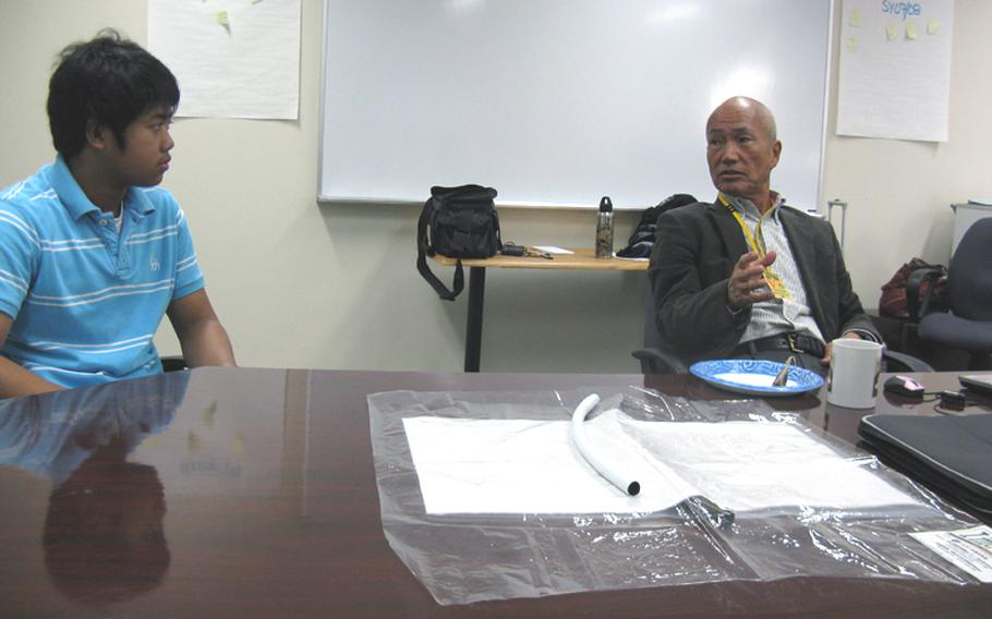 Yuichi Mori, right, explains his hydrogel-based system of growing plants to Yokosuka Middle School 8th-grader Christian Parros, 14, Thursday at the school. School officials hope to use the technology to teach students about nutrition and agriculture.