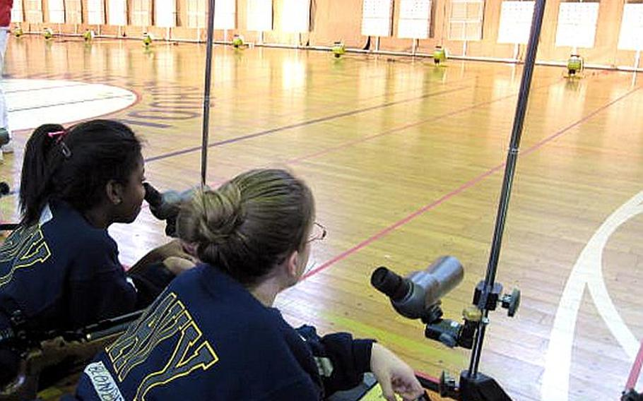 Two cadets prep themselves before firing their air rifles as cadets from throughout the Pacific competed in the first Far East DODEA Pacific JROTC Marksmanship Championships at E.J. King High School on Sasebo Naval Base, Japan.