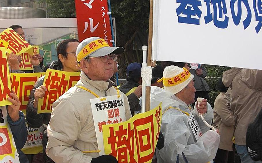 """Kazuo Nakamoto, 70, of Naha holds a sign that reads """"Drop (the Henoko plan)"""" during a protest Friday in front of the Okinawa prefectural government office. About 500 people showed up to protest Prime Minister Naoto Kan's visit to the island."""