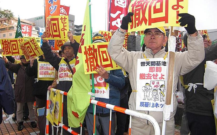 """Kazuo Nakamoto, foreground, 70, of Naha holds a sign that reads """"Drop (the Henoko plan)."""" About 500 people gathered Friday in front of the Okinawa prefectural government office to protest Prime Minister Naoto Kan's visit to the island."""