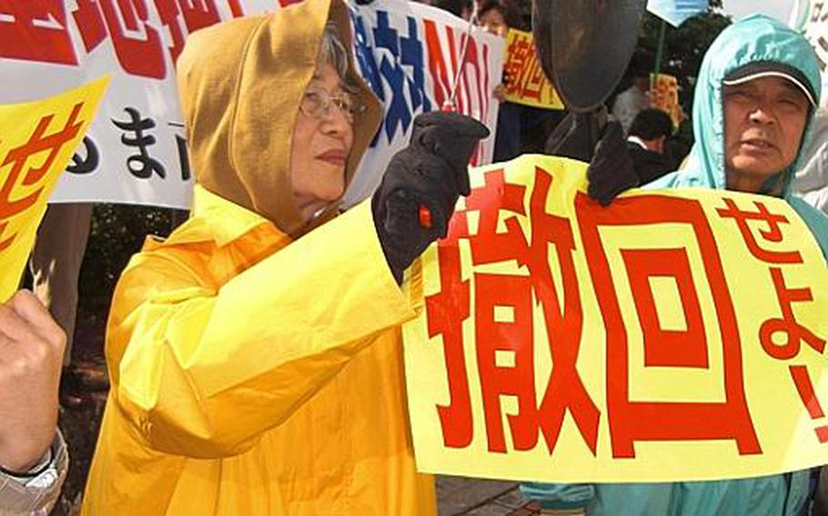 Fusae Nakazato of Naha bangs a pan with a spatula during a protest Friday in front of the Okinawa prefectural government office.