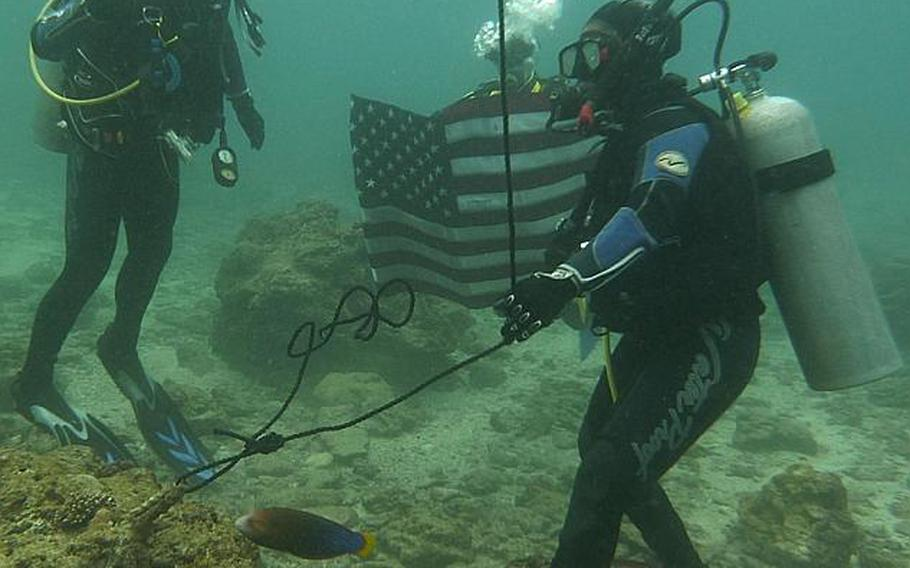 Okinawa-based Army Sgt. Juanita Tompkins, right, re-enlists underwater during a ceremony conducted Wednesday by Col. Lance. R. Koenig, left, Commander 10th Support Group and Army on Okinawa.