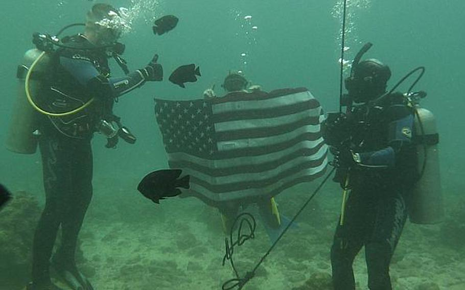 Okinawa-based Army Sgt. Juanita Tompkins, right, re-enlists underwater Wednesday in a ceremony conducted by Col. Lance. R. Koenig, left, Commander 10th Support Group and Army on Okinawa.