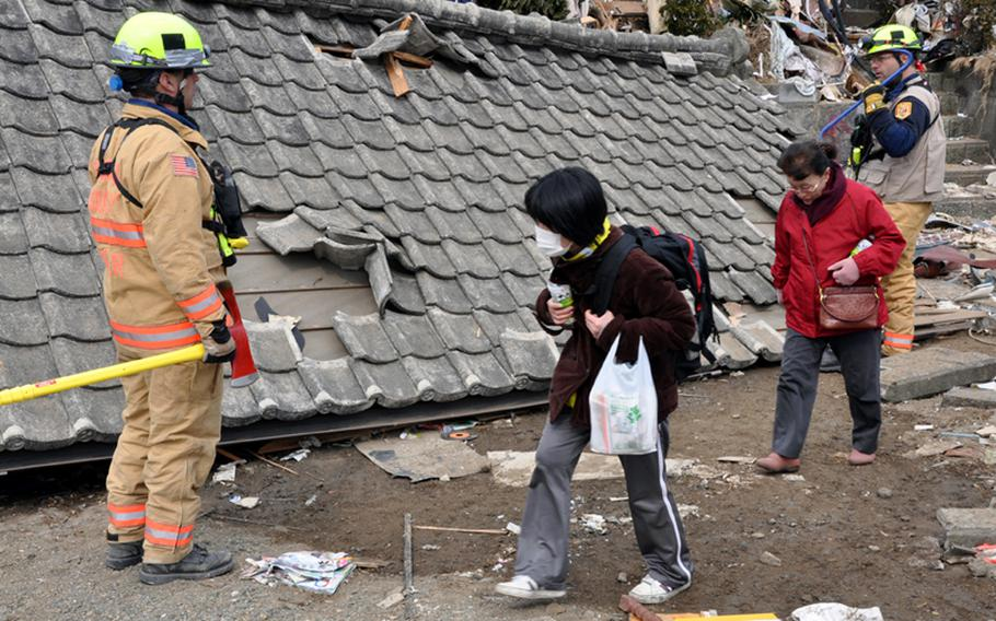 Residents of Ofunato village, Japan, pass search-and-rescue personnel who were combing the collapsed houses and acres of debris for survivors of the March 11 earthquake and follow-on tsunamis that ravaged the fishing port.