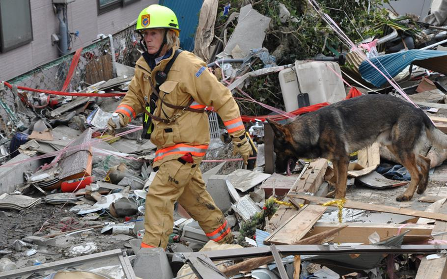 Rescue worker Elizabeth Kreitler and her search dog, Racker, on Tuesday work their way through the debris of a one of nearly 3,500 homes destroyed March 11 when an earthquake and follow-on tsunamis ravaged the coastal fishing town of Ofunato, Japan.