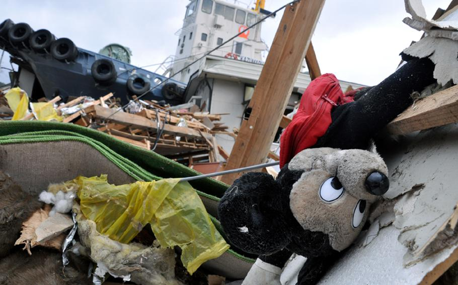 A Mickey Mouse doll sits in rubble in front of a tug boat that landed in the middle of a residential neighborhood in Ofunato village, Japan, during a March 11 earthquake and follow-on tsunamis.