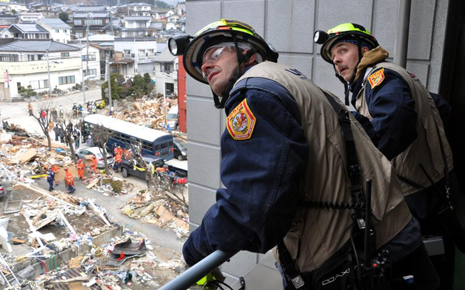 Virginia-based search-and-rescue workers look for the best way to get on top of an apartment building in the fishing village of Ofunato, Japan, during earthquake and tsunami relief efforts Tuesday morning.