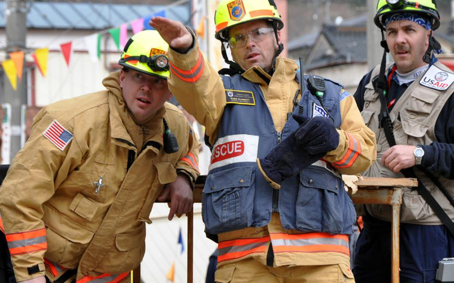 From left, Bob Zoldos, Mark Plunkett and Bobby Ritchie, members of a Fairfax, Va.-based search-and-rescue unit, gesture toward earthquake and tsunami damage on Tuesday morning in Ofunato, Japan.