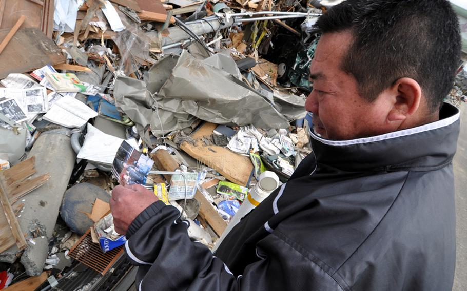 Takushi Tokai, a resident of Ofunato, Japan, looks at a picture of his family he found near the wreckage of his house on Tuesday. Nearly 3,500 homes were totally destroyed when a earthquake and tsunamis hit the fishing village on Friday.