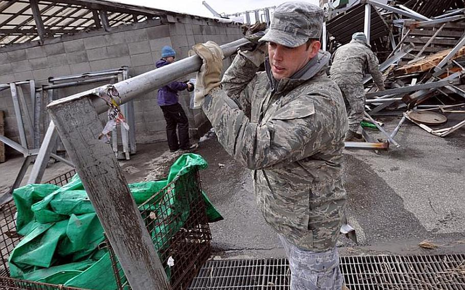 Tech. Sgt. Gregory Bird lugs metal frames across the parking lot of the Hachinohe fishing port during a volunteer clean-up session. Hundreds of volunteers were in the port as part of Operation Tomodachi, a U.S. Forces Japan initiative to provide humanitarian relief efforts to local communities following the March 11 devastating earthquake and follow-on tsunami that ravaged northeastern Japan.