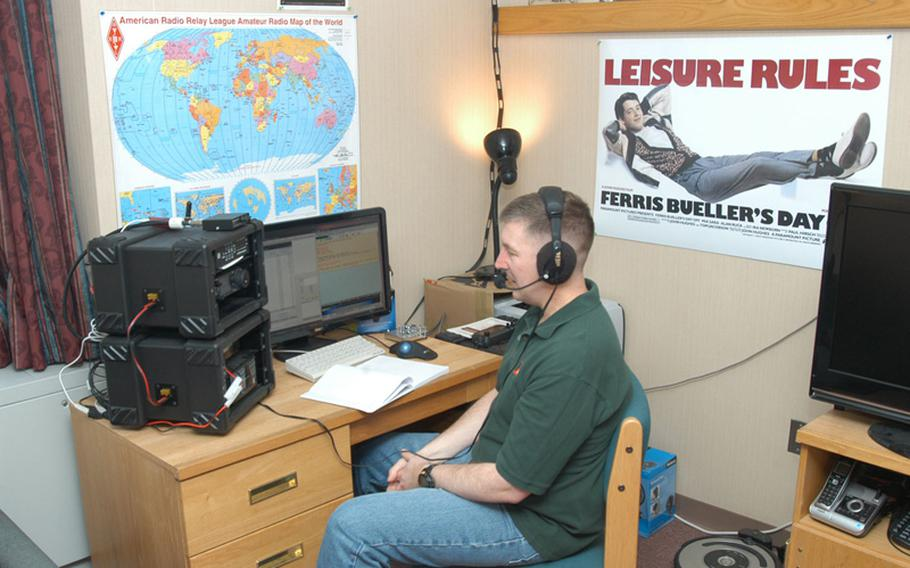 U.S. Army Maj. Scott Hedberg talks on the ham radio he has set up in his barracks room at Camp Red Cloud in South Korea.