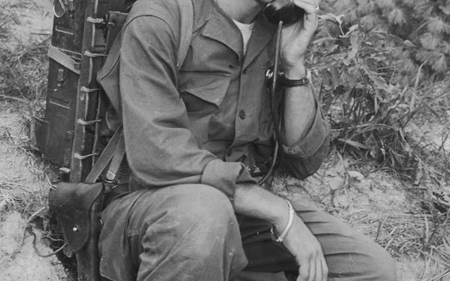 In this photo from 1950, Cpl. John Myrick of Nashville, Tenn., assistant communications chief of courageous Love Company of the 7th Infantry Regiment, 3rd Division, illustrates the use of the Army's SCR 300 radio during action for which the unit was commended by Supreme Allied Commander Gen. Matthew R. Ridgway.
