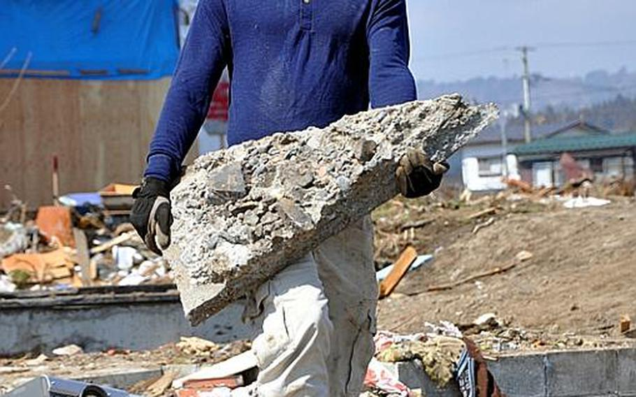 Civilian volunteer Alex Chamberlain, a member of the Misawa Air Base community, lugs a big chunk of concrete while helping clean the tsunami-ravaged Noda Village during a base-sponsored trip on Friday.