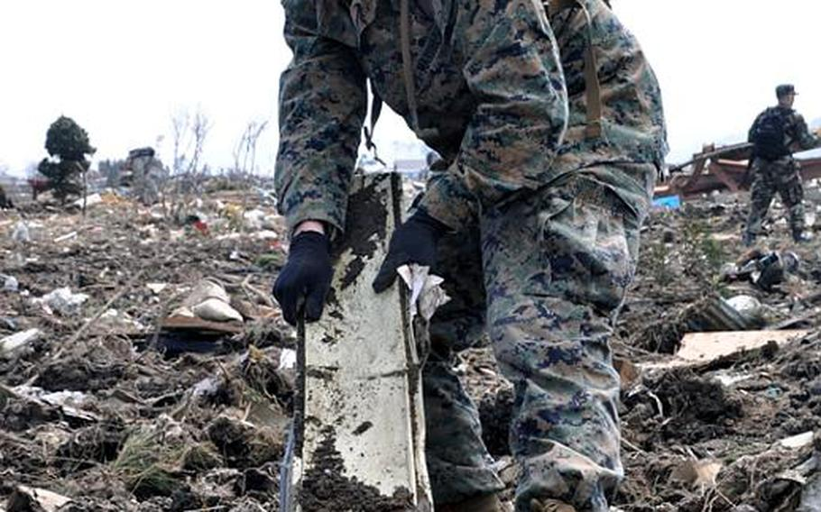 Lance Cpl. Garrett Williams pulls a strip of metal out of a massive debris field formed after a tsunami ripped through Noda Village, in Iwate prefecture, Japan, on March 11. The 20-year-old Marine and father of a 7-month-old said pulling kids' toys from the destroyed neighborhood was especially tough.