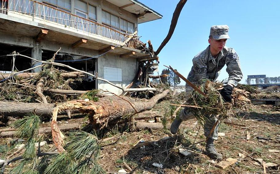 Air Force Staff Sgt. Samuel Clem, with the 35th Communications Squadron at Misawa Air Base, Japan, cleans debris from Noda Village on Friday.