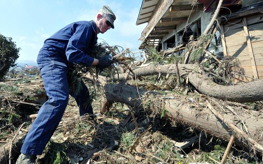 Air Force Master Sgt. Chris Burch pulls debris out of an area of Noda Village on Friday. Burch and Capt. Tyler Harris are in charge of volunteer clean-up trips from Misawa Air Base into surrounding Japanese communities.