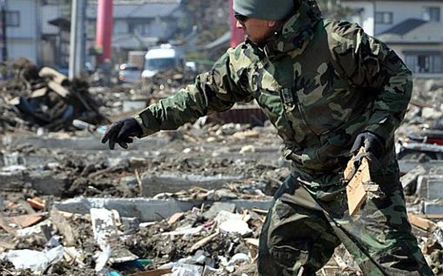 Tech. Sgt. Luis Cantu helps remove debris Friday from a destroyed neighborhood in Noda Village, about a two-hour drive south of Misawa Air Base. The fishing village was ravaged by a March 11 earthquake and tsunami.