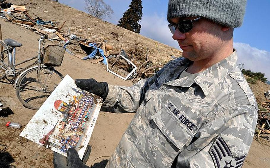 Staff Sgt. Chris Grogean, on temporary duty to Misawa Air Base, Japan, from Okinawa, reads the front of a picture discovered in the debris of Noda village on Friday. Grogean, who learned to speak Japanese while working as an English teacher previously in Japan, volunteered to serve as a translator on Friday's trip two hours down the coast from the base. In addition, a Japanese employee from the base volunteered Friday, making communication with village officials even easier.