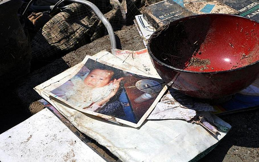 Small piles of valuables -- things such as pictures or written documents -- were dotted across a work site Friday at Noda village as volunteers cleaned a tsunami-stricken neighborhood.