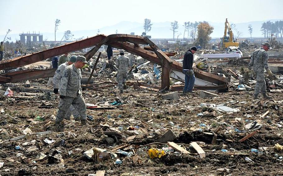 Volunteers from Misawa Air Base, Japan, trudge through the debris field they had been tasked with cleaning Friday at Noda village, about a two-hour drive south of the base. Village officials thanked the volunteers for their work.