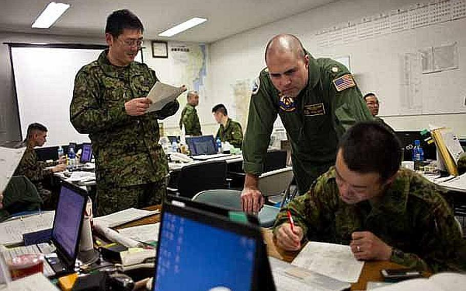 Lt. Cmdr. Barnet Harris, assigned to the Bilateral Crisis Action Team at Camp Sendai, Japan, works with Japan Self-Defense Force troops to coordinate U.S. and Japanese relief efforts.