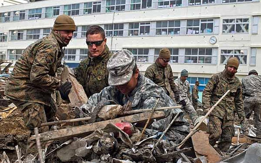 Spc. Christina Lee, 25, (right) and Lance Cpl. Dylan Messner, 20, along with other Marines and soldiers  from Okinawa, Camp Fuji and Camp Zama assist in the clean up of the Minato Elementary School in Ishinomaki, Japan, April 2, 2011.
