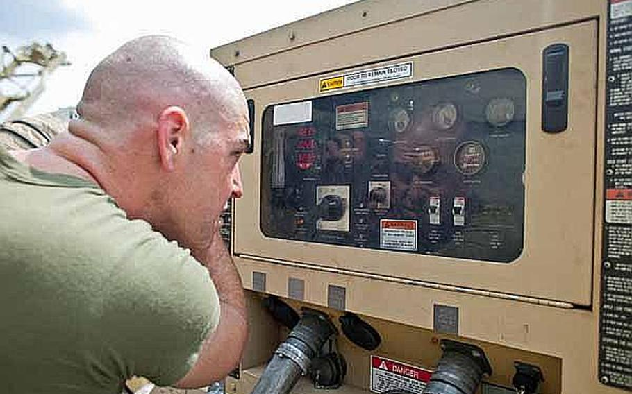 Marine Corps Capt. Jason Smith, the communications officer of Combat Logistics Regiment 35 out of Okinawa, Japan, cuts his hair using a generator control panel window as a mirror at the temporary camp set up at the Sendai Airport.