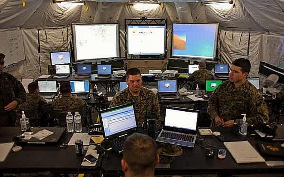 Marine Corps Staff Sgt. David Elbon, center, the arrival and departure air control group chief, talks with co-workers in the command and control center at the temporary U.S. military camp set up at the Sendai Airport in Sendai, Japan.