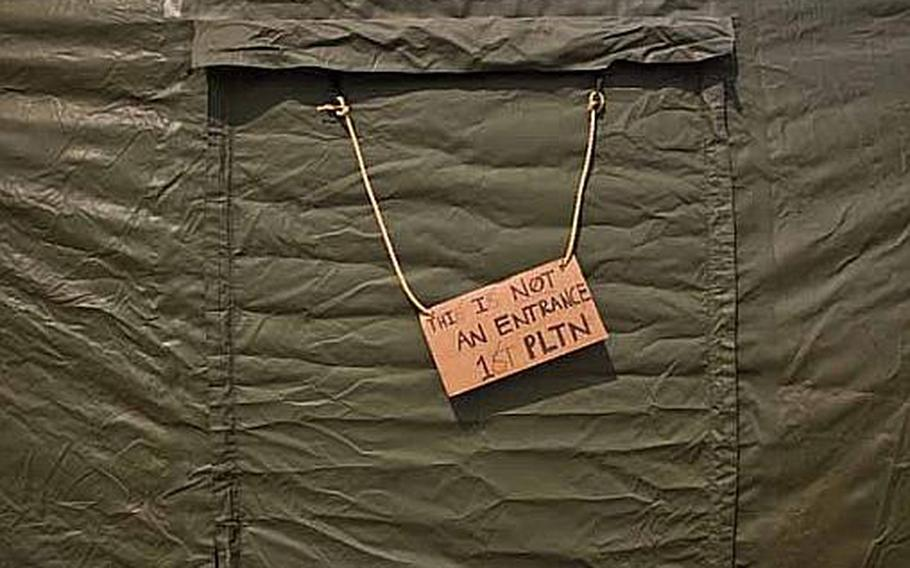"""A sign that reads, """"This is not an entrance-1st Platoon,"""" hangs outside the rear entrance to a tent at a temporary camp set up at Sendai Airport in Sendai, Japan. The base is home to about 200 Marines and soldiers, out of Okinawa and camps Fuji and Zama as well as a few Airmen out of Hawaii."""