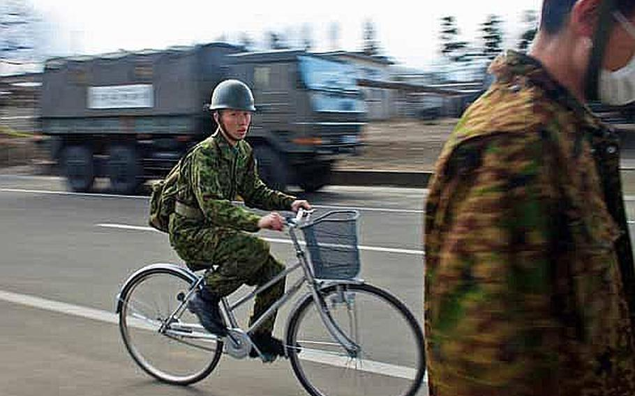 A soldier with the Japan Self-Defense Force rides his bicycle through a street at Camp Sendai, Japan.