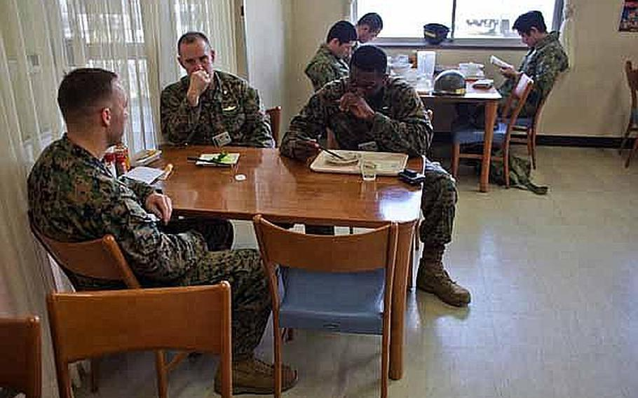 Three Marine Corps officers eat lunch at a diner at Camp Sendai, Japan as Japan Self Defense Force troops read manga after finishing their meals.