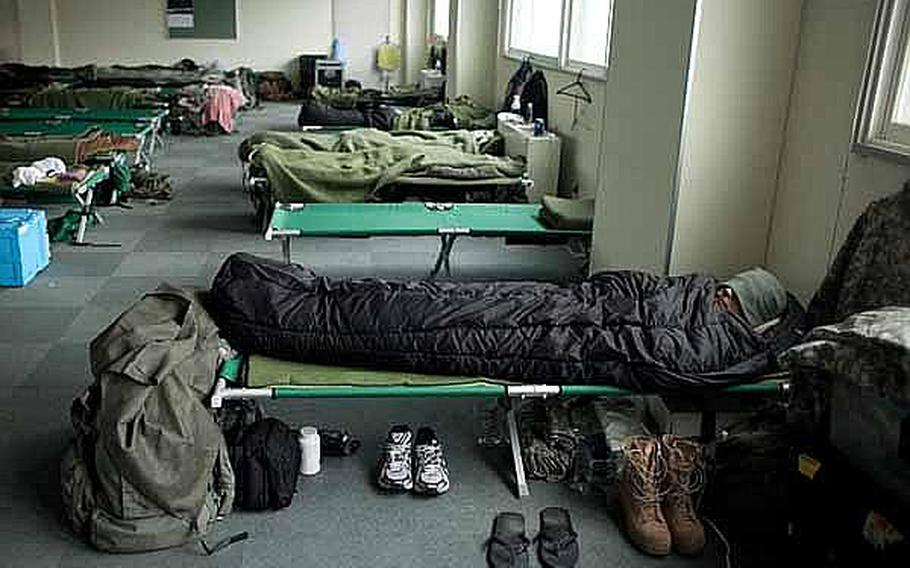 A soldier, along with Marines and troops from the Japan Self-Defense Force, sleeps in a male berthing at Camp Sendai, Japan.