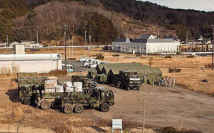 Soldiers begin to set up their new base of operations on the grounds of the Ishinomaki General Sports Park, in Ishinomaki, Japan, which Japan Self-Defense Force troops have already established as a main base for area troops. These soldiers along with almost 100 others are moving from their previous base at Sendai Airport, officials said.