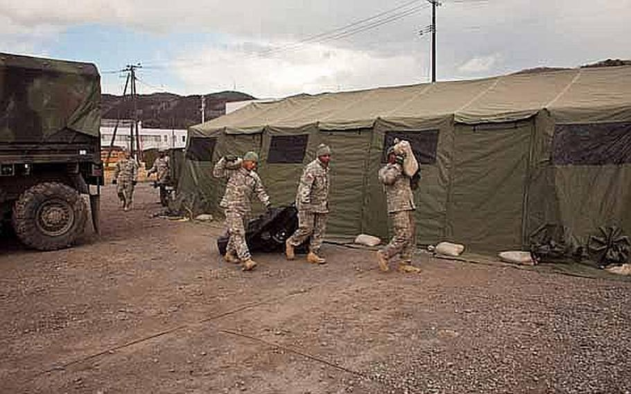 Soldiers begin to set up their new area base of operations on the grounds of the Ishinomaki General Sports Park, in Ishinomaki, Japan.The soldiers, along with almost 100 others, are moving from their previous base at Sendai Airport.