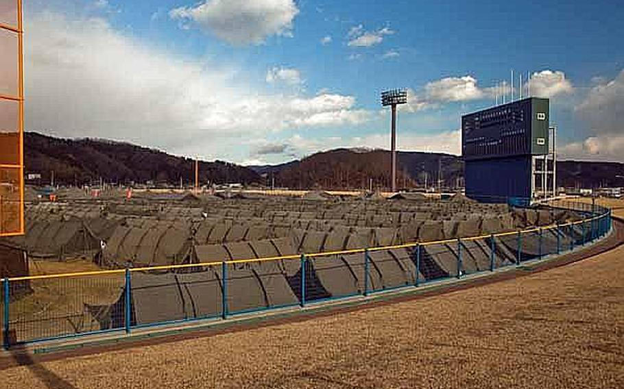 Japan Self Defense Force tents fill the outfield of Ishinomaki General Sports Park in Ishinomaki, Japan, which has become the base of operations for the area. Approximately 100 U.S. Army soldiers moved from their camp at Sendai Airport to the stadium grounds.