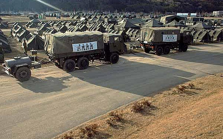 Japan Self-Defense Force vehicles and tents have taken over the Ishinomaki General Sports Park in Ishinomaki, Japan, which has become their base of operations for the area. Approximately 100 U.S. Army soldiers moved from their camp at Sendai Airport to the stadium grounds.