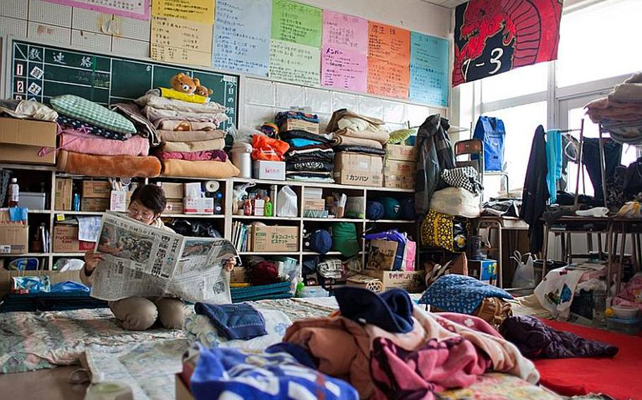 A displaced resident of the Kadonowaki Middle School shelter reads the newspaper after lunch.