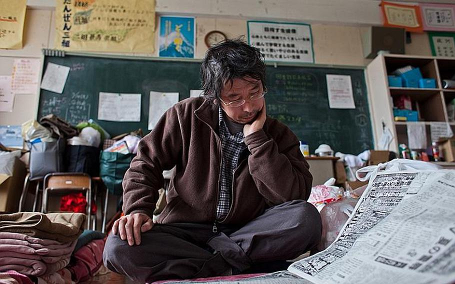 Hidetoshi Oikawa, a dental technician whose home and place of work were destroyed in the March 11 tsunami, reads a newspaper at the Kadonowaki Middle School shelter in Ishinomaki, Japan.