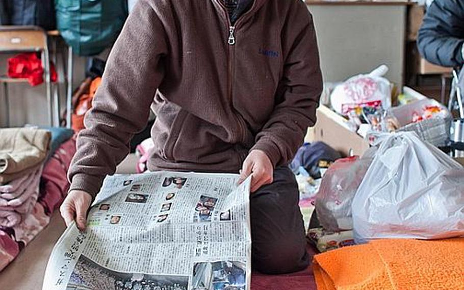 Hidetoshi Oikawa, a dental technician, who now lives at the Kadonowaki Middle School shelter in Ishinomaki, Japan, demonstrates, using an alarm clock as his home and the newspaper as the water, how the March 11 tsunami destroyed his home.