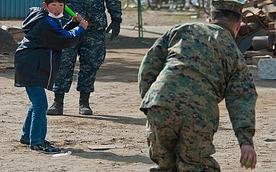 U.S. troops from Okinawa and Camp Fuji play baseball with children at the Watanoha Elementary School shelter in Ishinomaki, Japan, after helping clean up the school grounds as well as deliver aid provided by the Christian relief organization Samaritan's Purse. The U.S. military has also been coordinating with other NGOs to deliver aid, officials said.